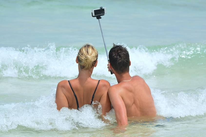 Man taking selfie of himself and his partner on the beach