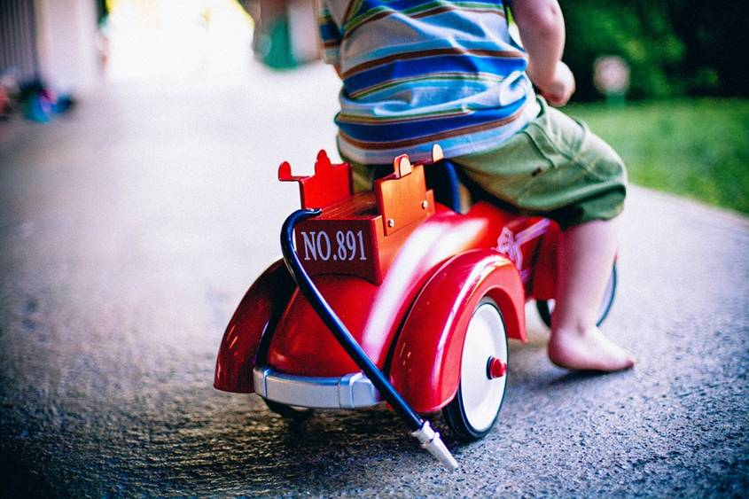 Toddler boy riding a fire engine tricycle