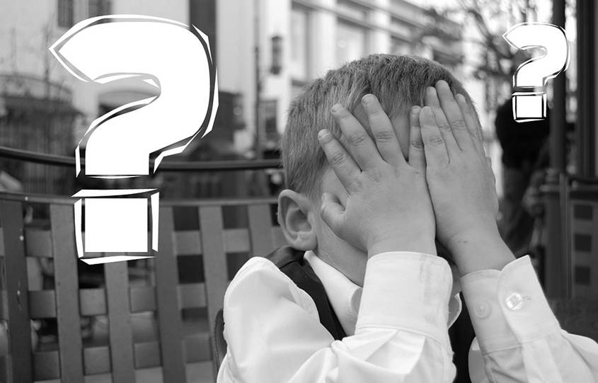 Boy hiding his face with question marks around his head