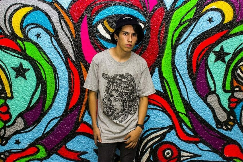 Teenage boy in front of graffiti