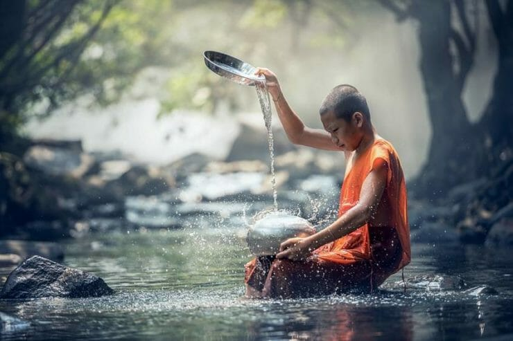 Buddhist monk child pouring water in a stream
