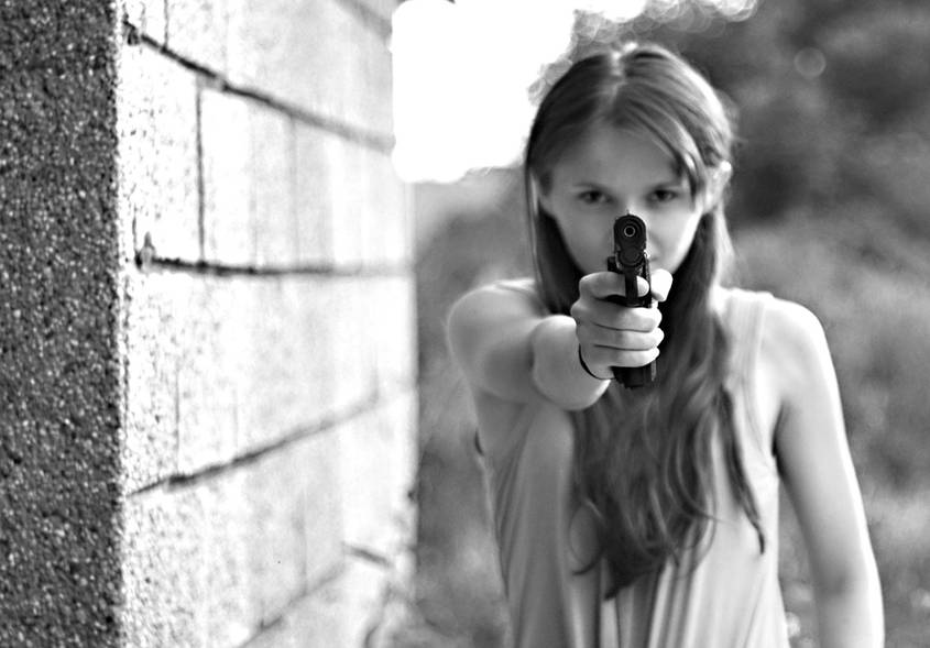 Teenage girl holding a gun