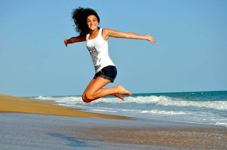 Young woman jumping for joy on a beach