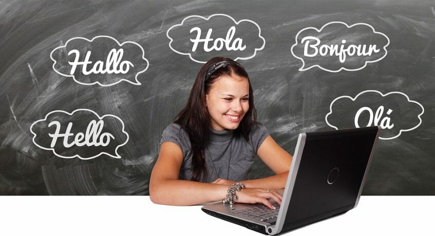 Girl on the computer with the word Hello in several languages