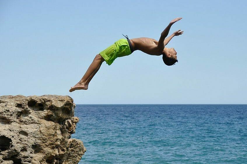 Teenage boy diving backwards off a cliff
