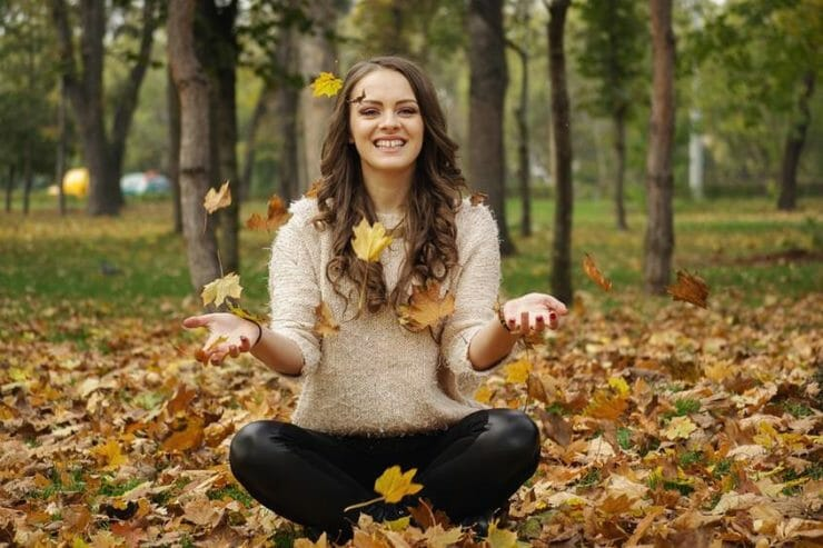 Happy woman sitting in a forest