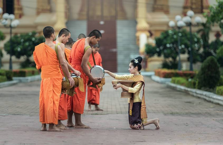 Woman giving offering to Buddhist monks