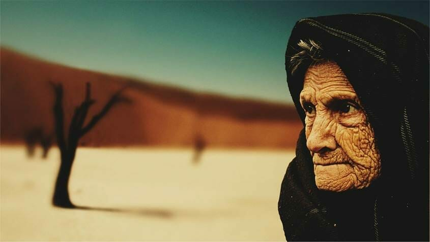 Old wrinkled woman in the desert