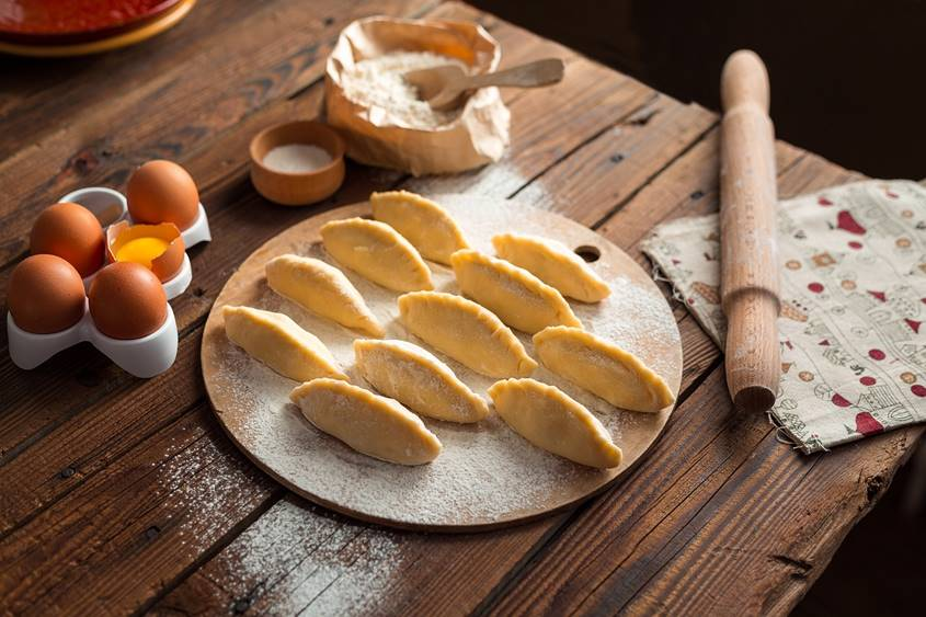 Dumplings, rolling pin, eggs and flour on a table