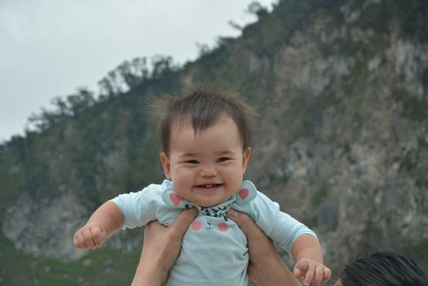 Baby girl smiling as she is lifted up