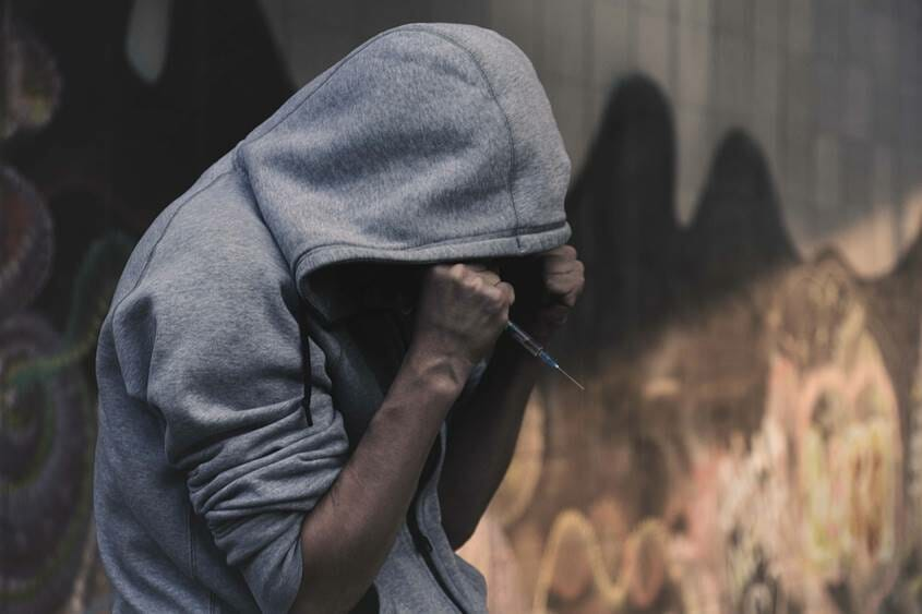 Man in hoodie holding a syringe