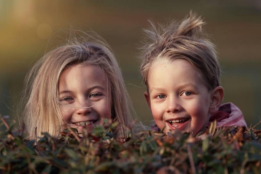 Boy and girl peeking over a hedge