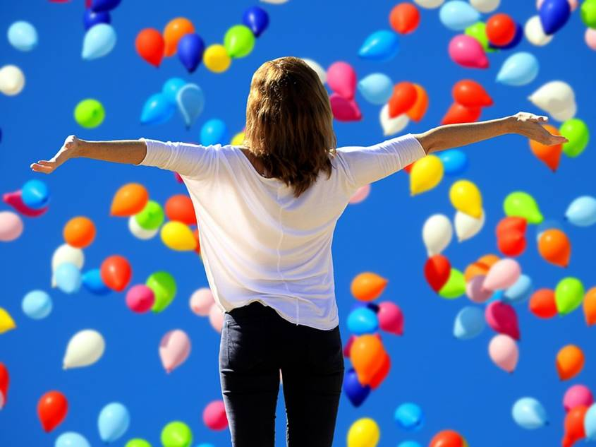 Balloons raining on a happy woman winner