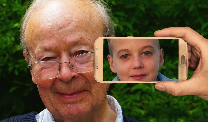 Mobile phone pointed at old man showing a boy