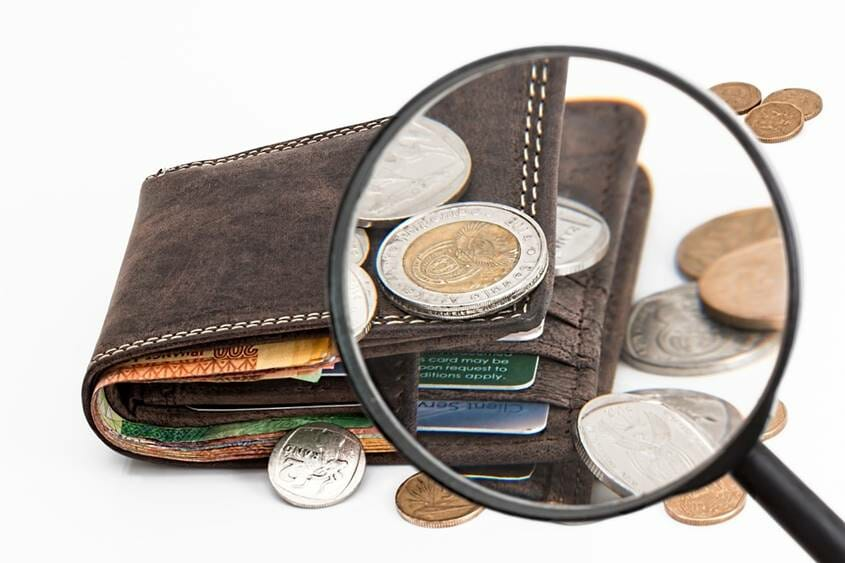 Magnifying glass looking at a wallet and coins