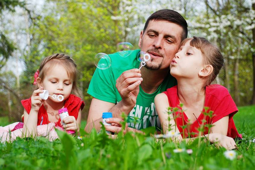Father and daughters blowing bubbles