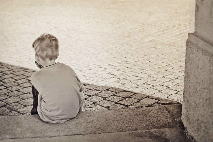 "Boy sitting sadly on a stone step after someone said to him ""I'm disappointed in you"""