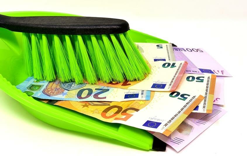 "Broom and dustpan with a pile of money notes as a symbol for""raking it in"""