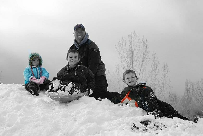 Father and 3 children enjoying the snow