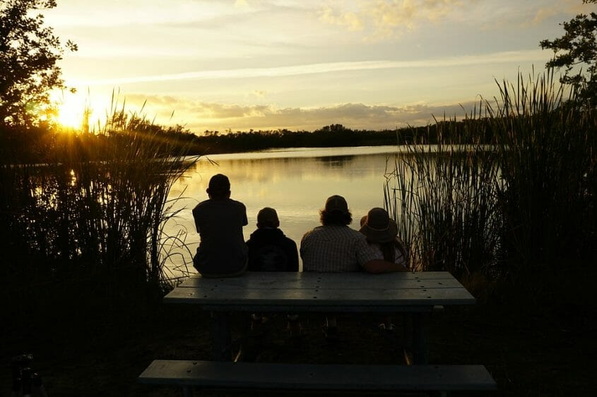 Family watching the sunset by a lake