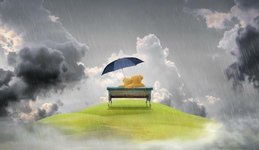 2 teddy bears cuddling on a bench under an umbrella in the rain
