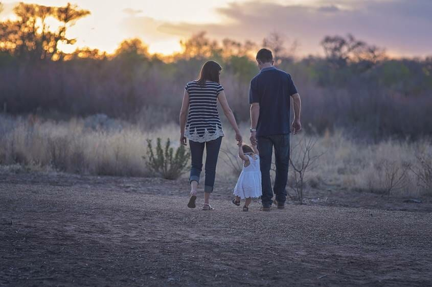 Parents walking in nature with young daughter