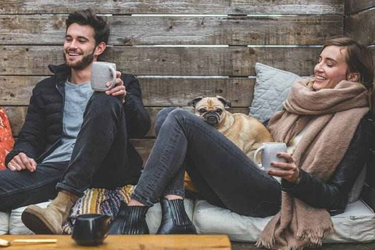 Couple laughing with hot drinks and dog
