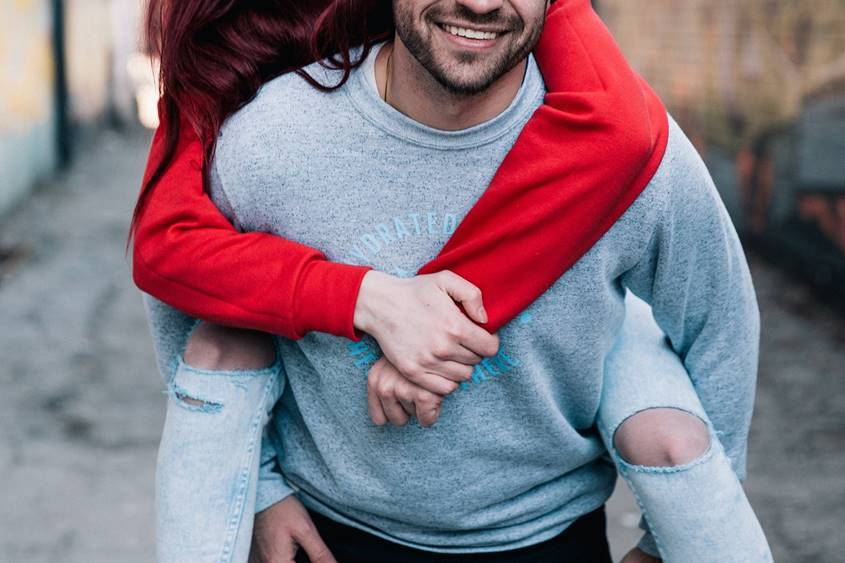 Young man carrying young woman on his back