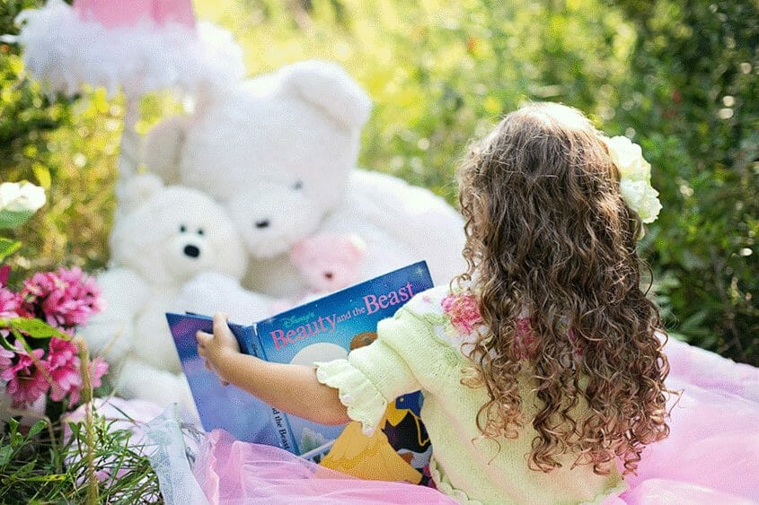 Girl reading a book to her stuffed animals