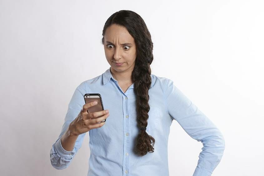 Woman looking upset with mobile phone in hand