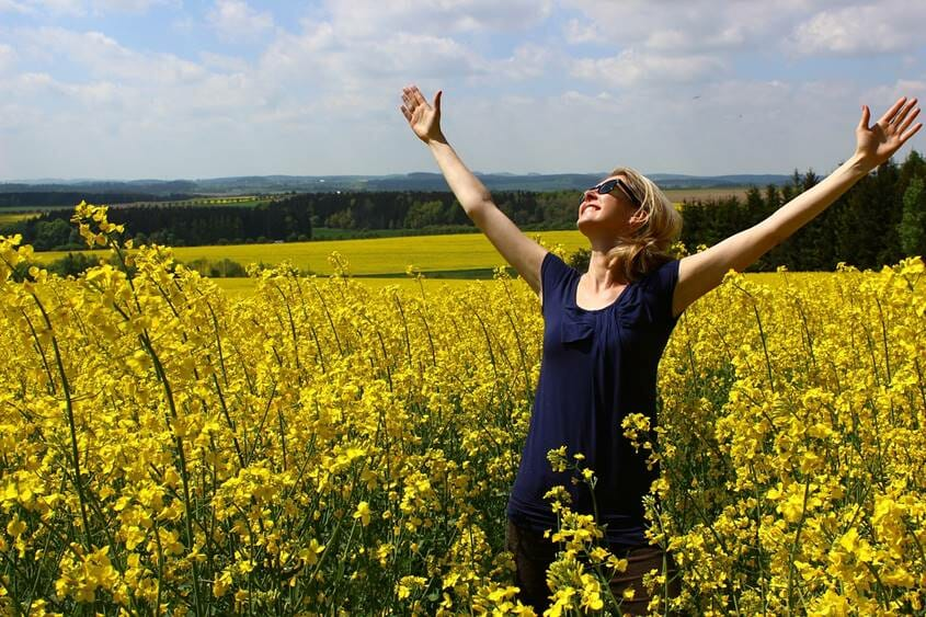 Happy woman with her arms open wide in a field of flowers