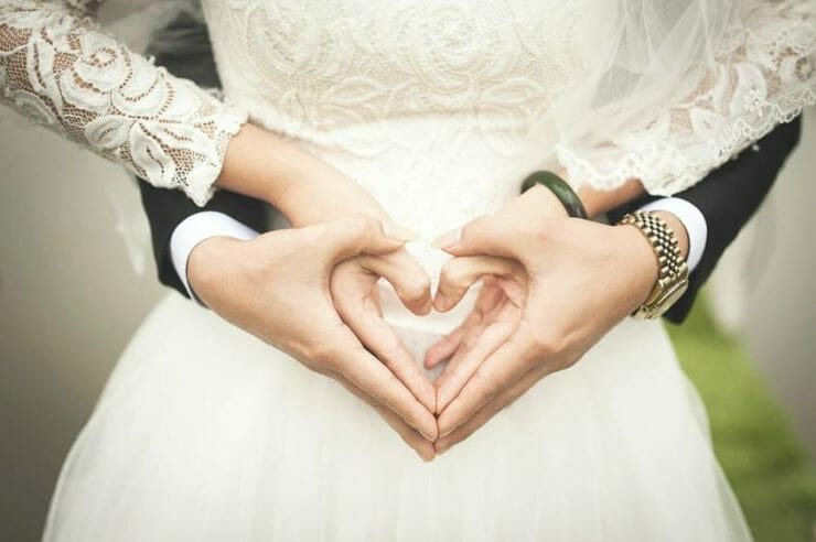 Bride and groom holding their hands in heart shape