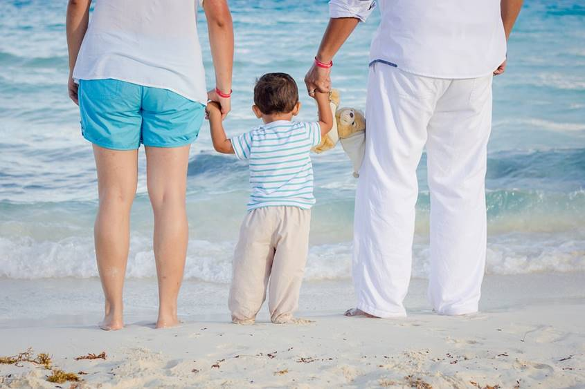 Parents by the ocean with their small boy