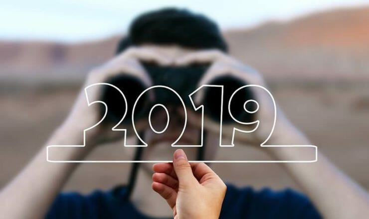 Man looking at 2019 through binoculars