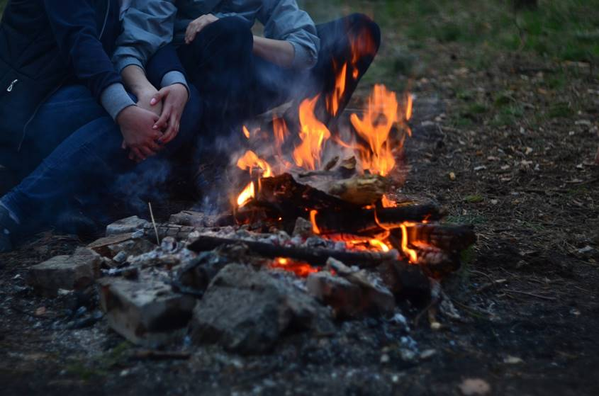 Couple warming up near a campfire