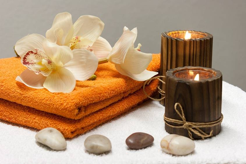 Towel, flowers, rocks and candles ready for pampering