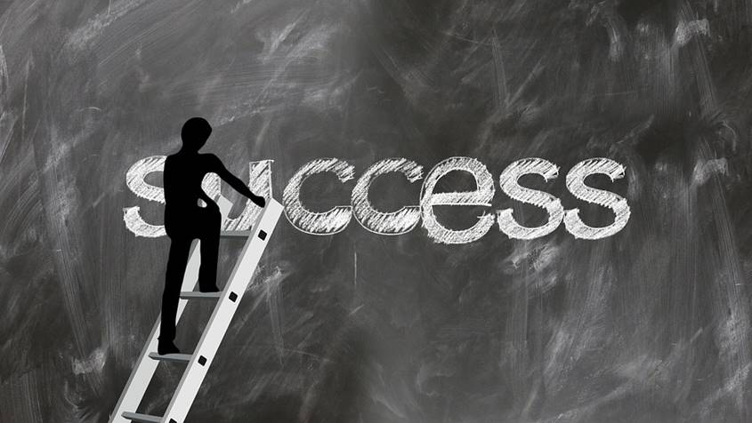 Figure climbing ladder up to the word Success