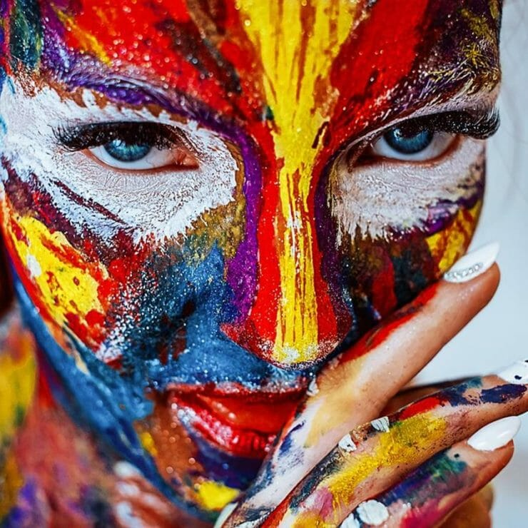 Woman covered in colorful pain like a bird