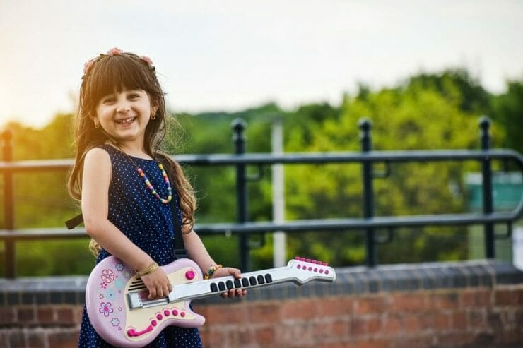 Girl smiling and playing guitar - kids coaching can do this for you too