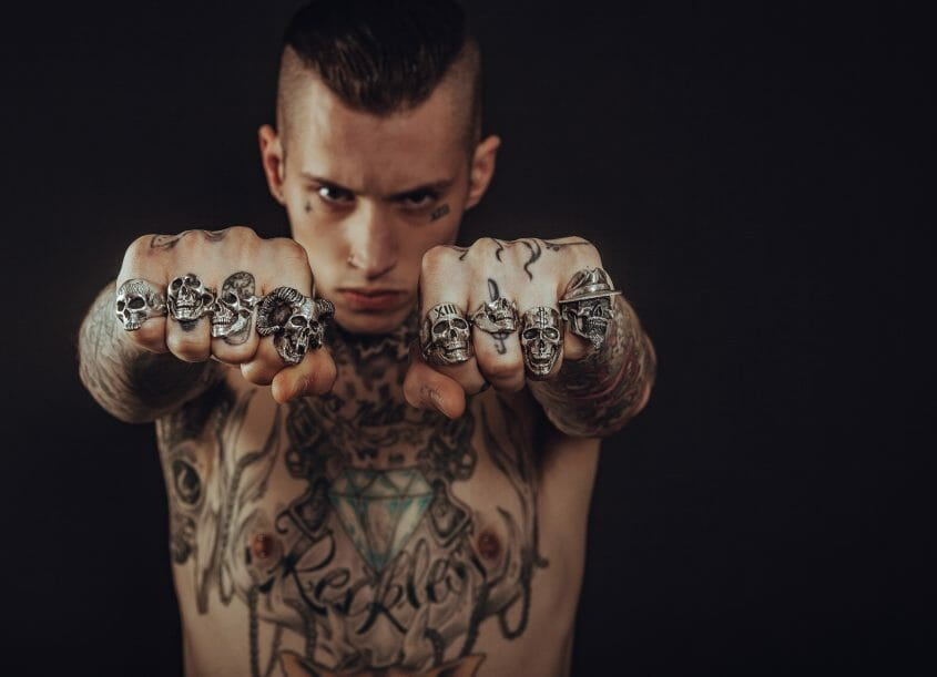 Young man with tattoos and skill rings (may or may not be abusive)