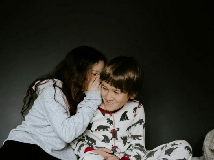 Girl in pajamas whispering to a boy in pajamas