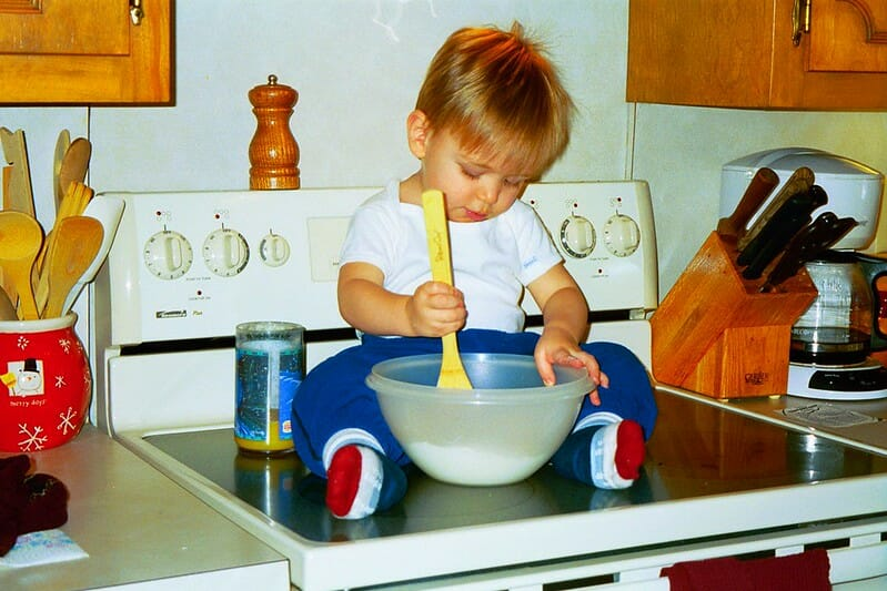 Little boy sitting on a stove stirring with a big spoon