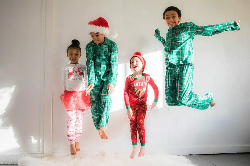 Kids jumping on a bed at a Christmas sleepover