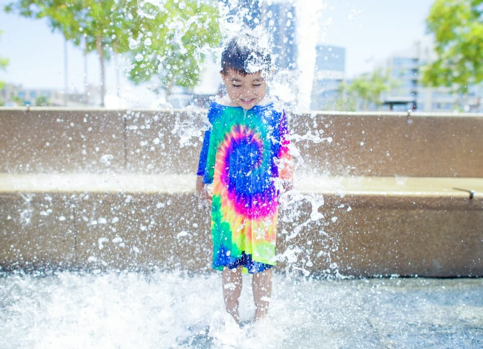 Happy boy in a water fountain