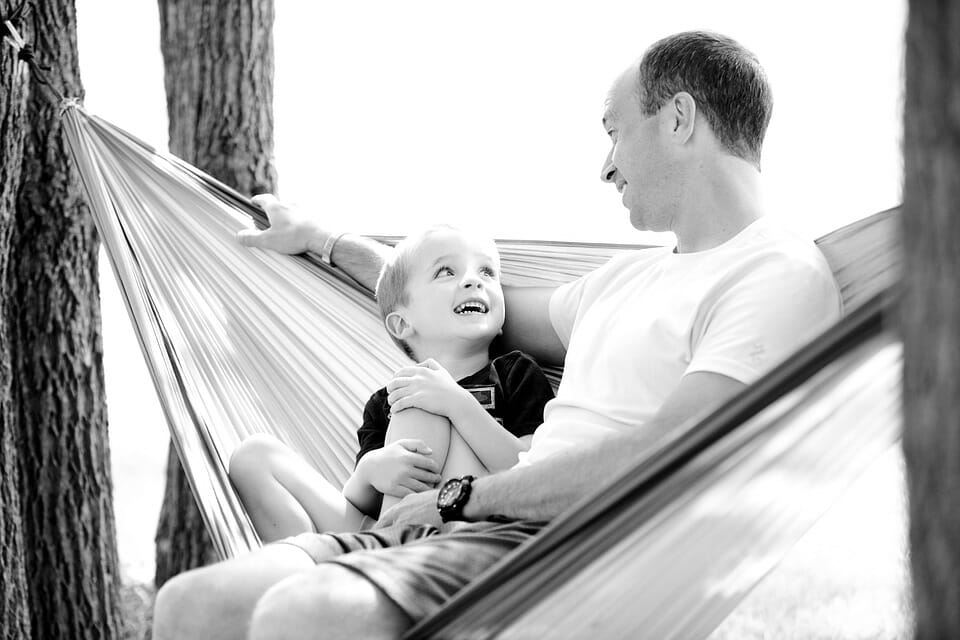 Happy boy on a hammock with his father
