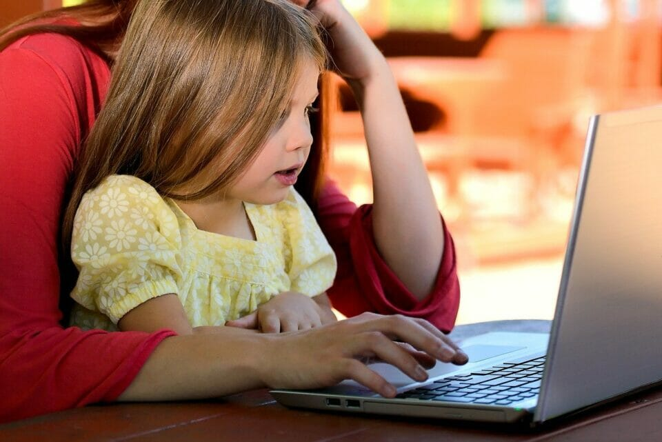 Little girl in her mother's lap in front of a laptop