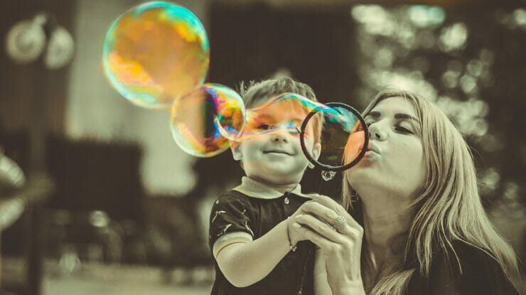 Woman and little boy blowing bubbles