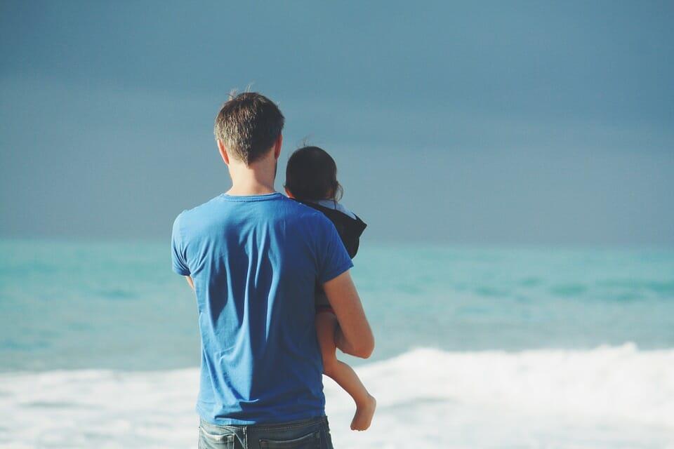 Man holding little girl on the beach