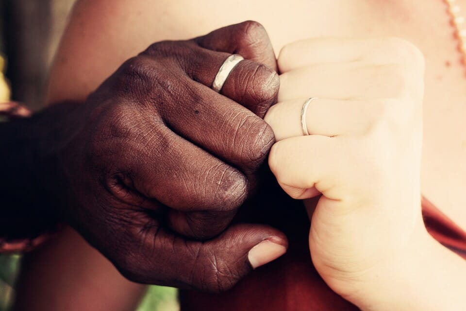 Black man and white woman's hands with wedding rings