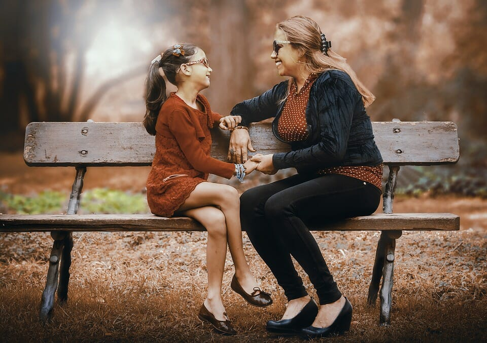 Woman and girl sitting on a park bench and smiling at each other